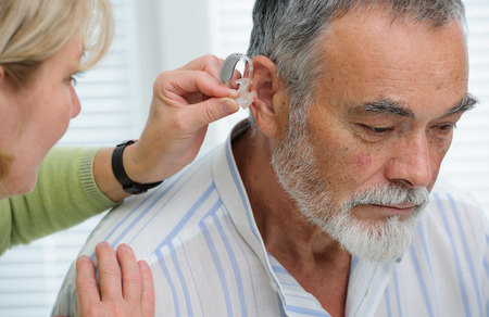 Doctor inserting hearing aid in senior's ear Stock Photo