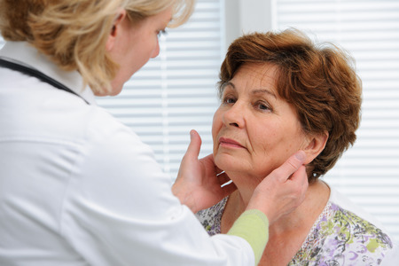 female doctor touching the throat of a patient in the office photo