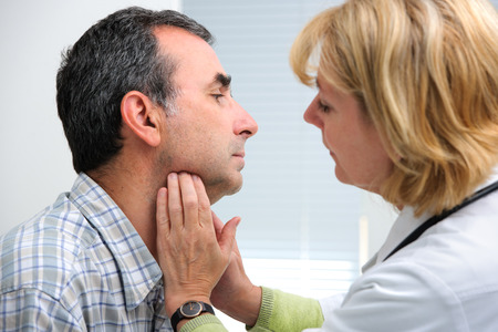 female doctor touching the throat of a patient in the office