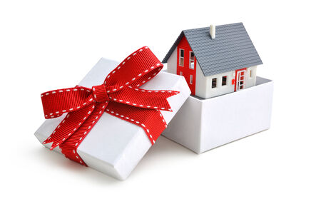 box construction: Model of a house in gift box with red ribbon Stock Photo