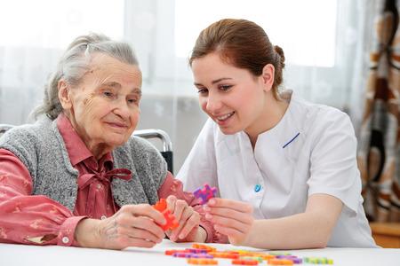 Elder care nurse playing jigsaw puzzle with senior woman in nursing home Stockfoto