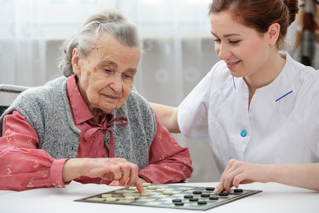 Senior woman playing checkers with a nurse in a retirement home photo