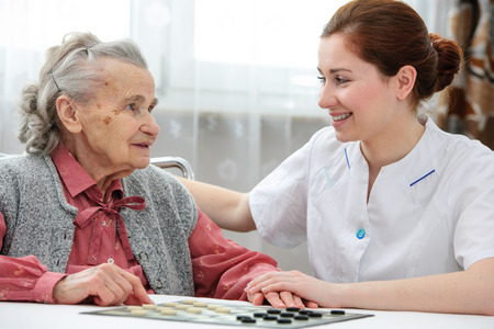 retirement age: Senior woman playing checkers with a nurse in a retirement home Stock Photo