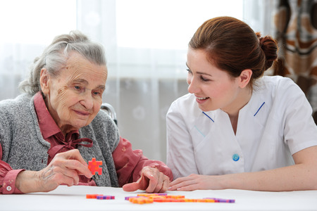Elder care nurse playing jigsaw puzzle with senior woman in nursing home Stockfoto