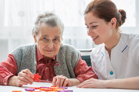 demented: Elder care nurse playing jigsaw puzzle with senior woman in nursing home Stock Photo