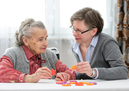Elder care nurse playing jigsaw puzzle with senior woman in nursing home Foto de archivo
