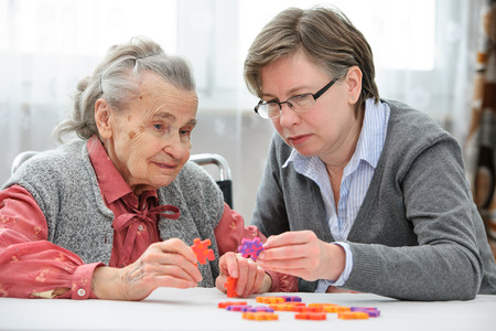 Elder care nurse playing jigsaw puzzle with senior woman in nursing home Foto de archivo
