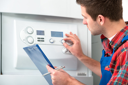 maintenance engineer: Technician servicing the gas boiler for hot water and heating