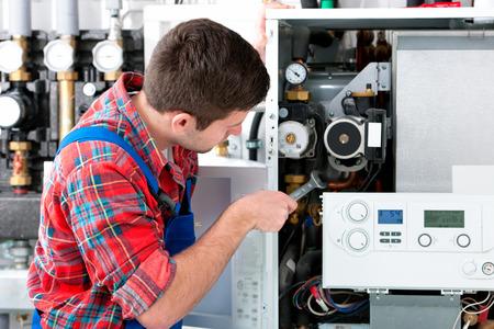sistemas: T�cnico de mantenimiento de la caldera de gas para agua caliente y calefacci�n Foto de archivo