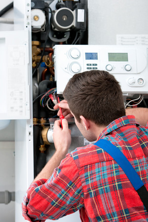 Technician servicing the gas boiler for hot water and heating
