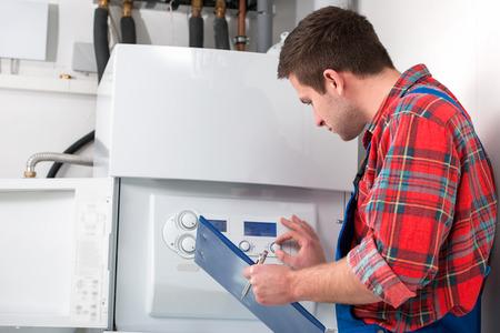 warm water: Technicus onderhoud van de gas boiler voor warm water en verwarming Stockfoto