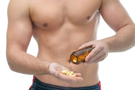 Atletische jonge man met behulp van bodybuilding supplementen. Sportvoeding