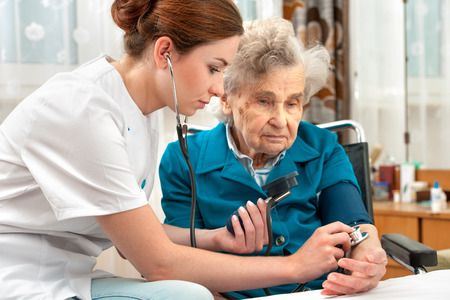 Female nurse measuring blood pressure of senior woman photo