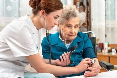 nursing care insurance: Female nurse measuring blood pressure of senior woman Stock Photo
