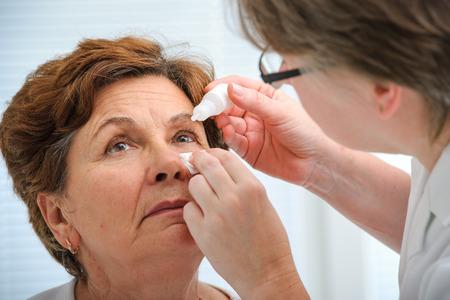 yeux: Docteur aide le patient et donne les gouttes oculaires Banque d'images