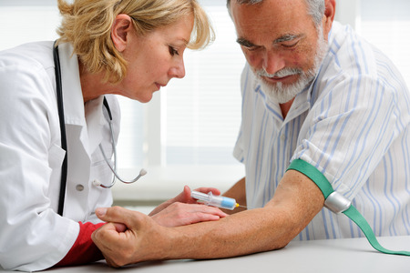nurse with syringe is taking blood for test at the doctor's office Stock Photo