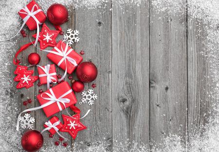 weihnachtsschleife: Geschenk-Boxen und Schneeflocken auf Holzuntergrund