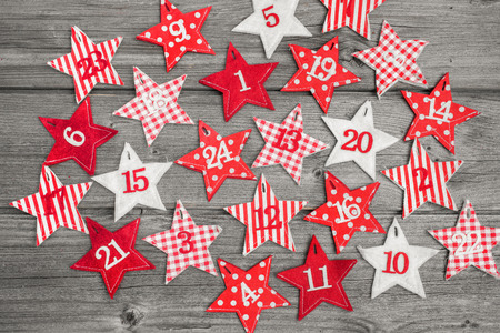 Advent calendar with stars on old wooden background photo