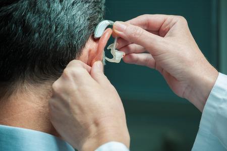 personas escuchando: M�dico de insertar el aud�fono en el o�do de la alta Foto de archivo