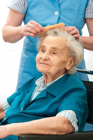 Pflegekraft putzt die Haare einer Frau. Haushaltshilfe Standard-Bild