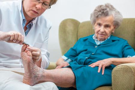pedicura: Enfermera ayuda a una anciana con la podología y el cuidado del cuerpo en casa