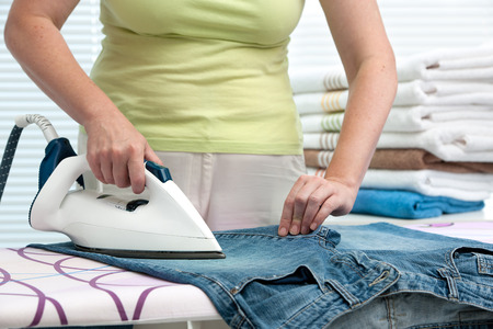 Close up of a woman ironing clothes with a steam iron photo