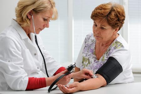 Doctor measuring blood pressure of female patient Banque d'images
