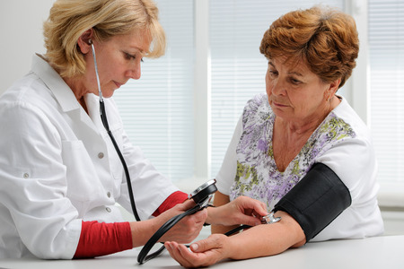 Doctor measuring blood pressure of female patient photo