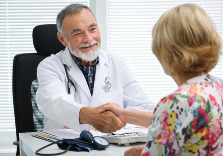 consulta médica: Cuide la sacudida de las manos con el paciente en la oficina