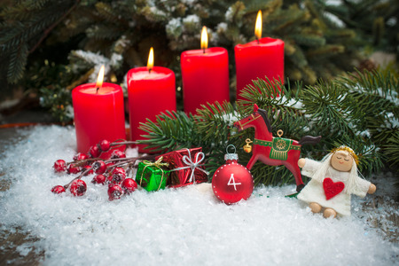 Christmas tree branches and candle for advent season four candles burning photo