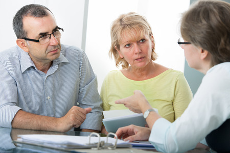 Couple getting financial advice from consultant at home photo