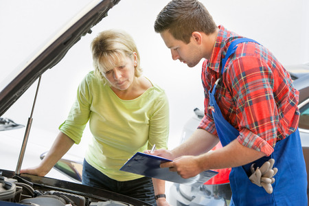 Auto mechanic and female customer in auto repair shop photo