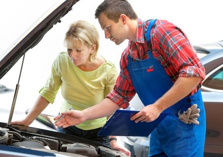 Mecánico de automóviles y el cliente femenino en taller de reparaciones auto