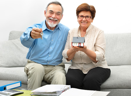 Happy senior couple holding a small house and keys in hands photo