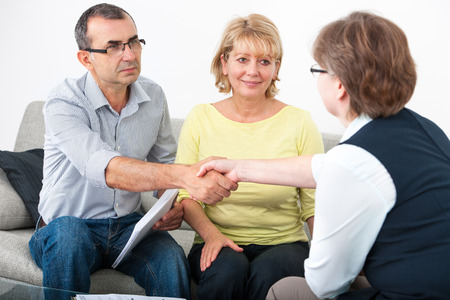 contract signing: Mature couple getting financial advice from consultant at home Stock Photo