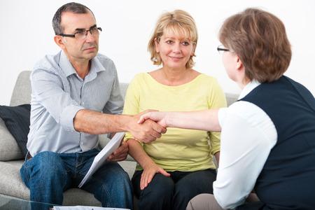 firmando: Pareja madura recibiendo asesoramiento financiero de consultor en casa
