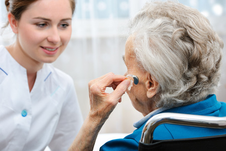 assisted living: Senior woman inserts hearing aid in her ear