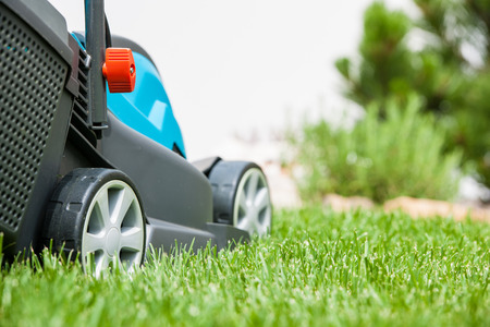 outside machines: Lawn mower on a green meadow. Gardening equipment