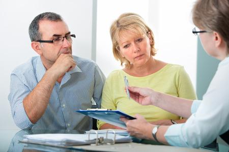 Volwassen paar krijgt financieel advies van consultant thuis Stockfoto