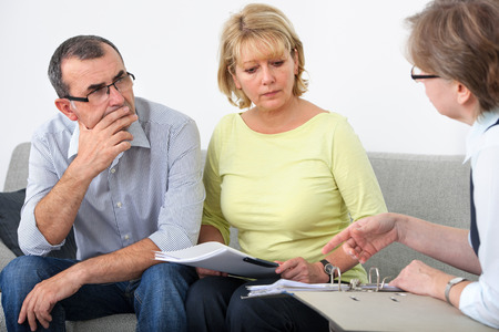 Mature couple getting financial advice from consultant at home Stock Photo
