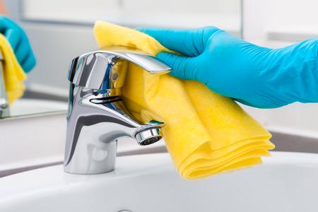 llave de agua: Mujer que hace tareas en el baño, la limpieza del grifo Foto de archivo