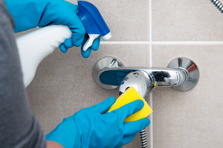 woman doing chores in bathroom, cleaning faucet with spray detergent photo