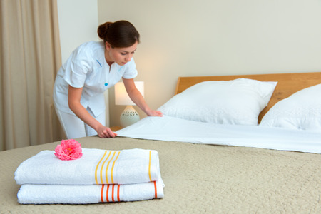 suite: Young maid changing bedclothes in a room Stock Photo