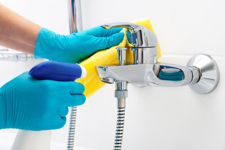 woman doing chores in bathroom, cleaning faucet with spray detergent