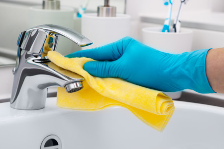 mujer limpiando: Mujer que hace tareas en el baño, la limpieza del grifo Foto de archivo