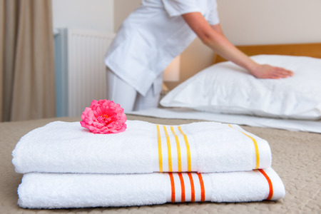 hotel suite: Young maid changing bedclothes in a room Stock Photo