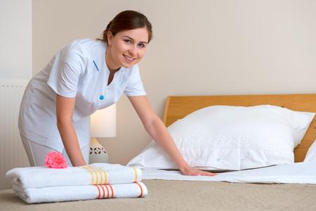 sirvienta: Dama joven cambiando la ropa de cama en una habitaci�n Foto de archivo