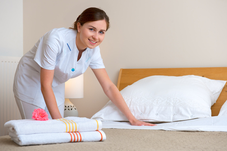 Young maid changing bedclothes in a room Stockfoto