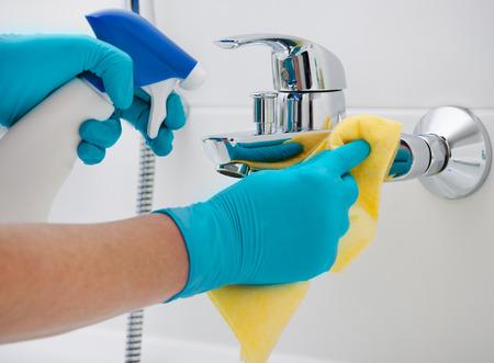 llave de agua: mujer que hace tareas en el baño, la limpieza del grifo con detergente aerosol