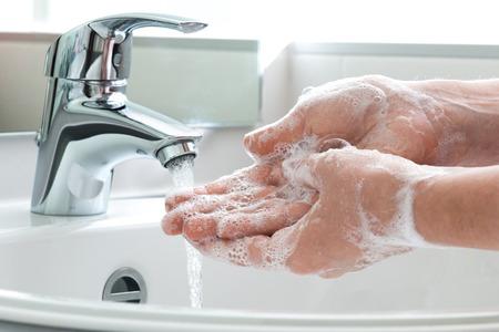 El lavado de manos con jabón bajo el grifo